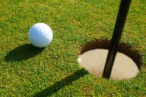 Close-up of golf ball on putting green.