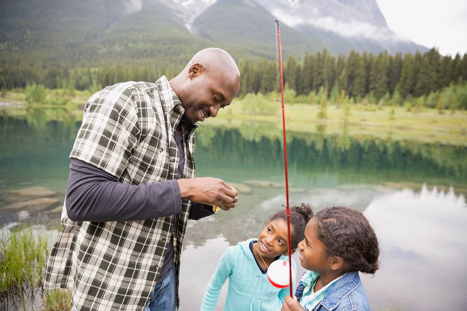 Father teaching daughters to fish at lakeside