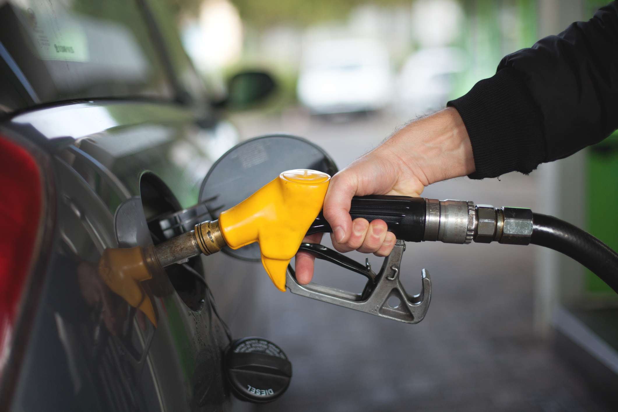 hand holding a yellow gas pump in a car