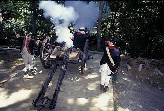 Actors dressed in military uniforms demonstrate live cannon firing techniques used at Yorktown.