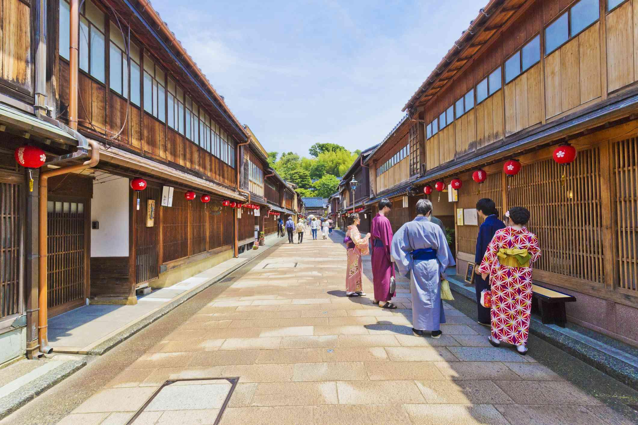 Geisha and men in traditional Japanese dress outside teahouses in Kanagawa's Higashi Chaya District