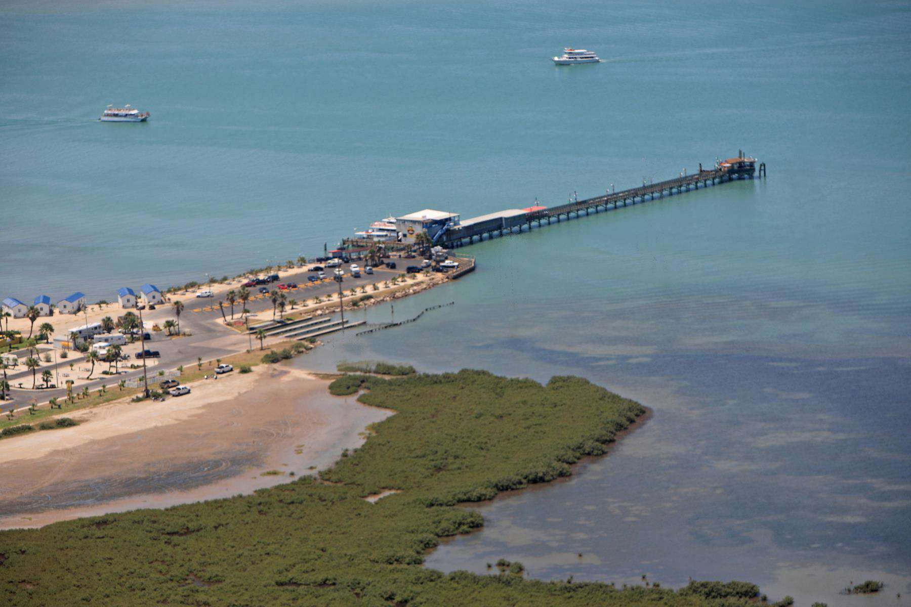The pier surrounded by the aquamarine waters of the Gulf