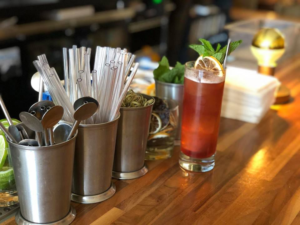 metal cups on a bar with metal spoons, bamboo skewers, and reusable straws. There is also a tall glass with a brown drink garnished with mint and lemon slice