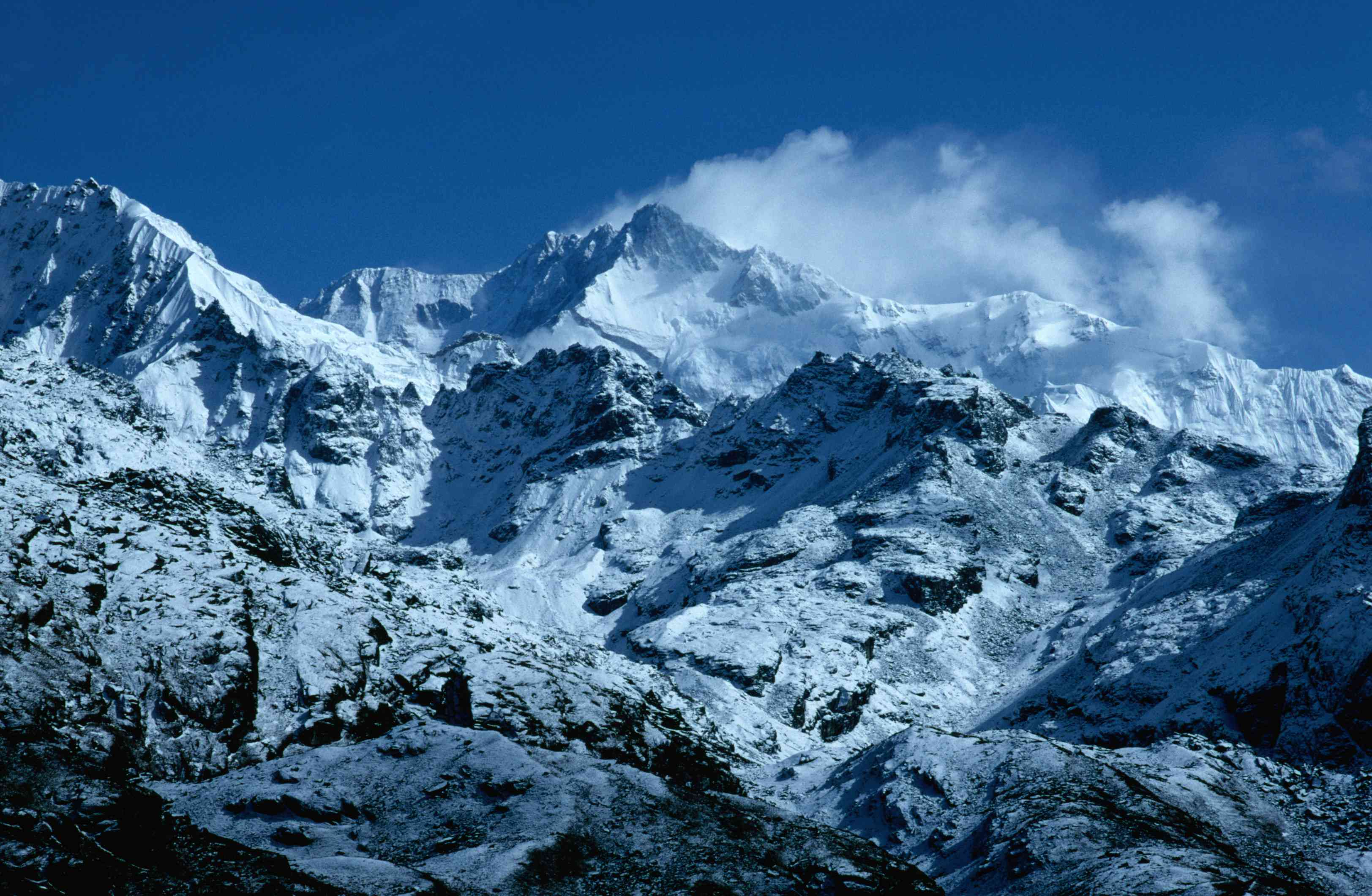 snow-capped mountains with clouds and blue sky