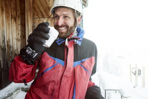 man in red ski jacket drinking hot beverage and smiling