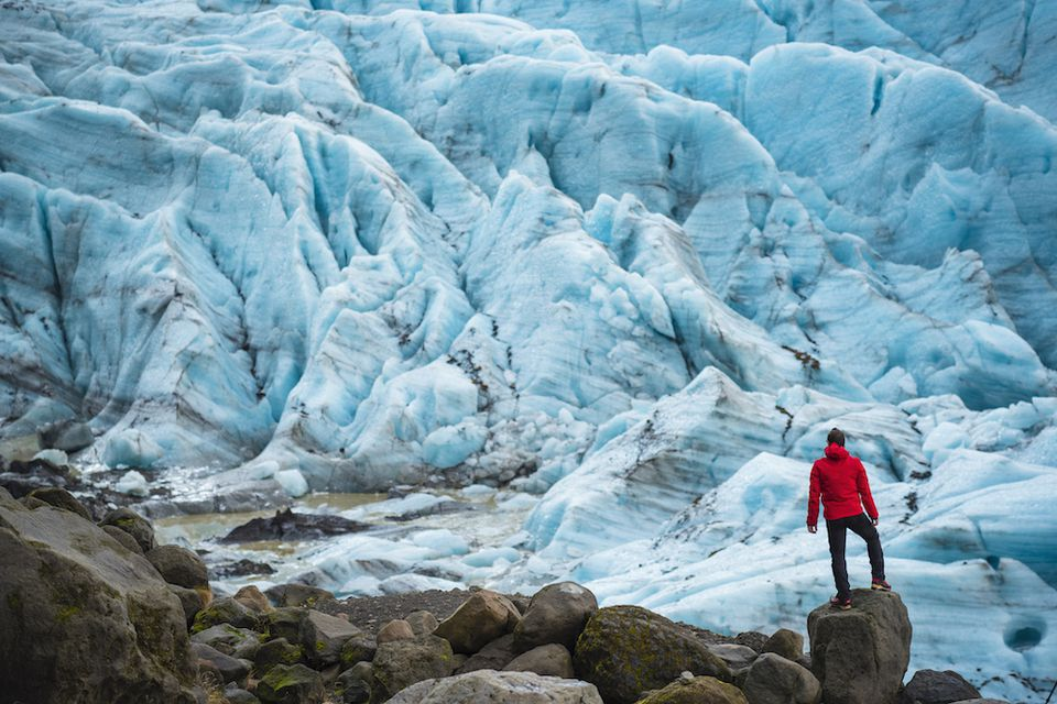 man standing in front of a glacier
