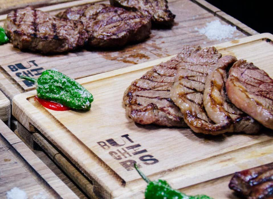Three cutting boards with steaks and a green chile on them