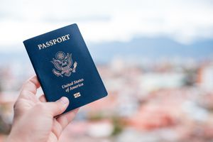 Close-Up Of Hand Holding American Passport Against Townscape