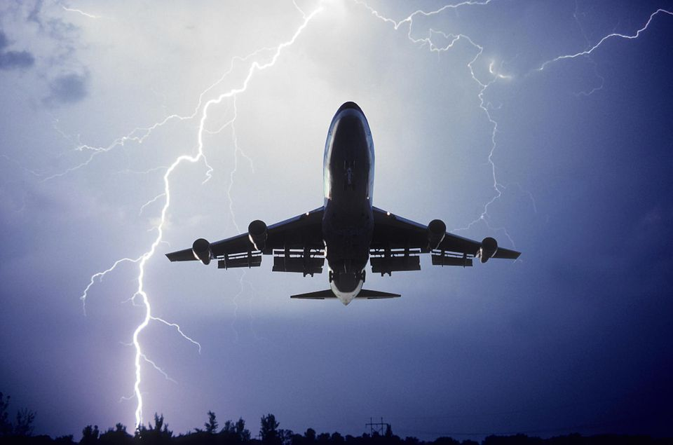 Airplane taking off with lightning in the sky