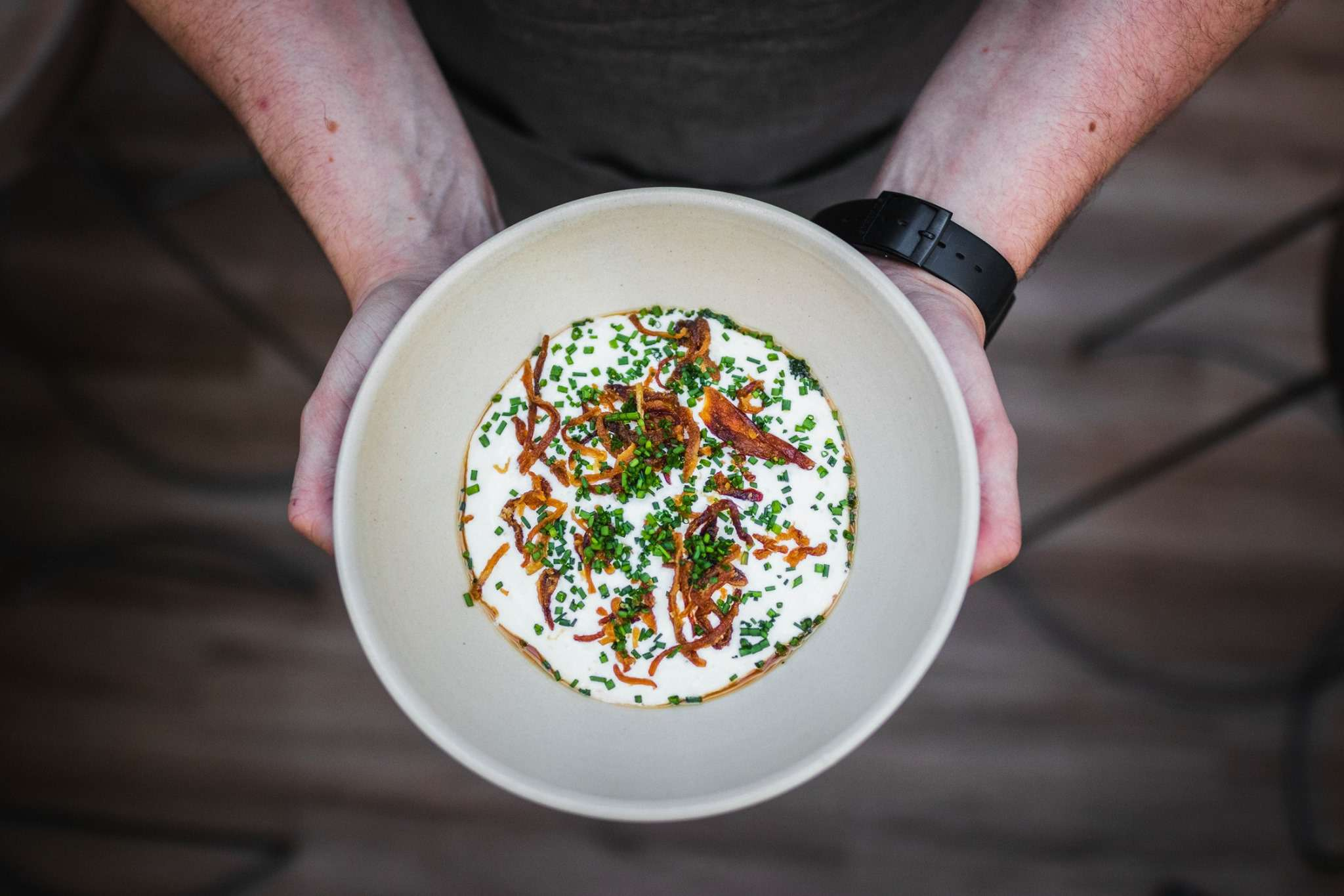 two hands holding a bowl of a white soup farbish with green herbs and crispy onions