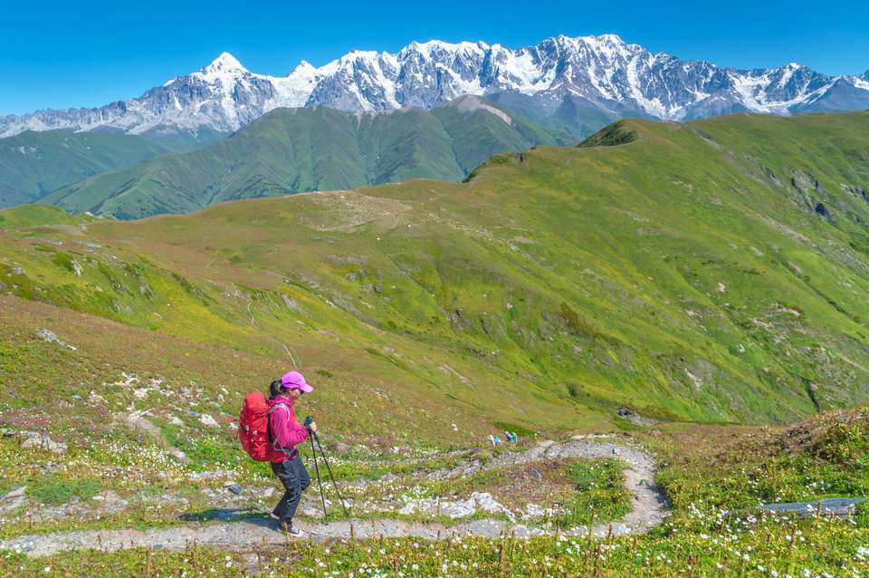 Female Hiker Descending Latpari Pass In Caucasus Mountains, Upper Svaneti, Georgia