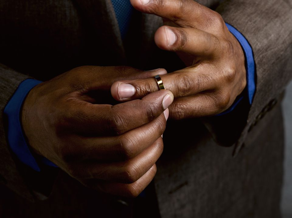 Business man putting on wedding band