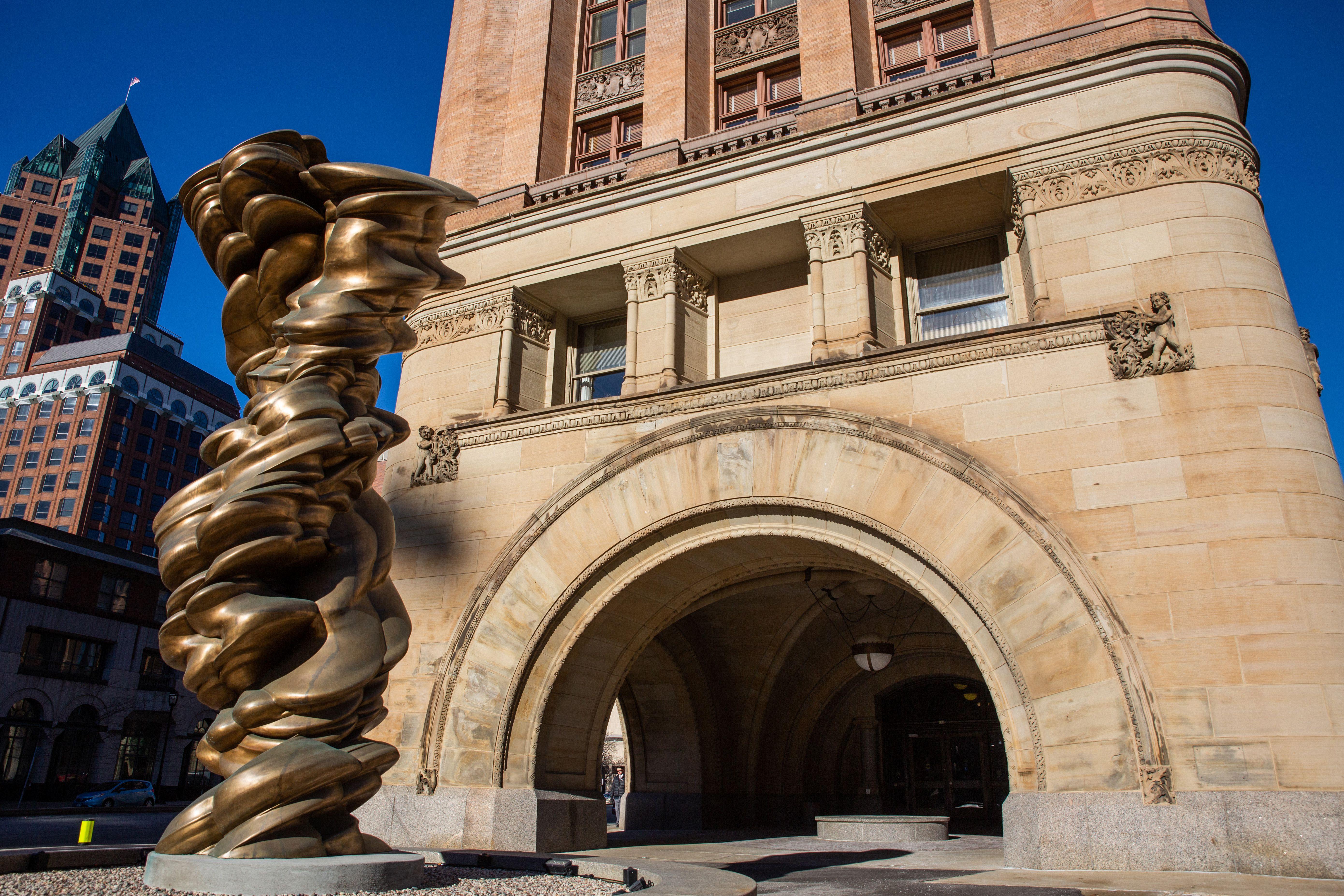 Exterior del ayuntamiento con una estatua pública de bronce en el frente