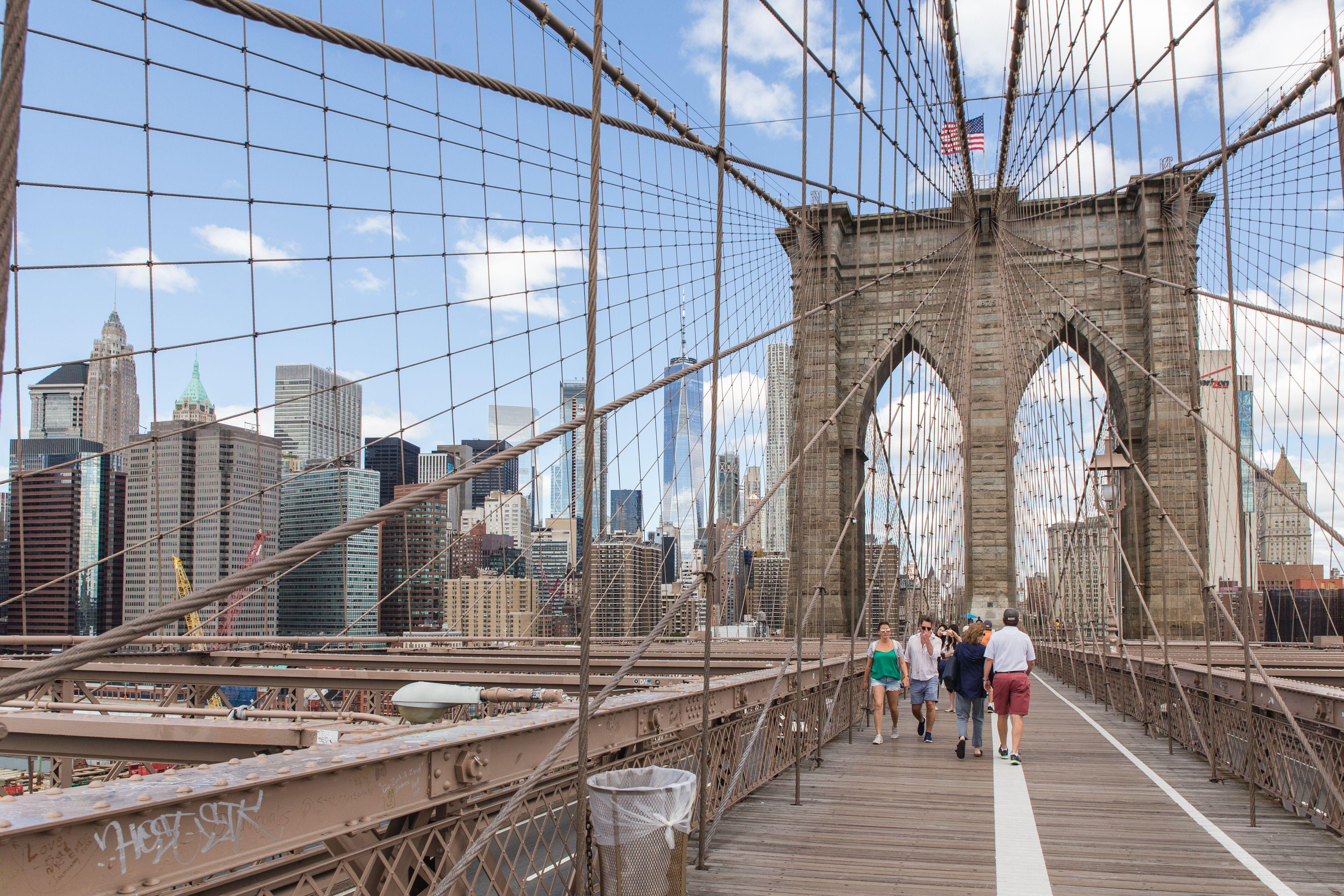 People walking through the Brooklyn Bridge , Vista de la estatua de la Libertad