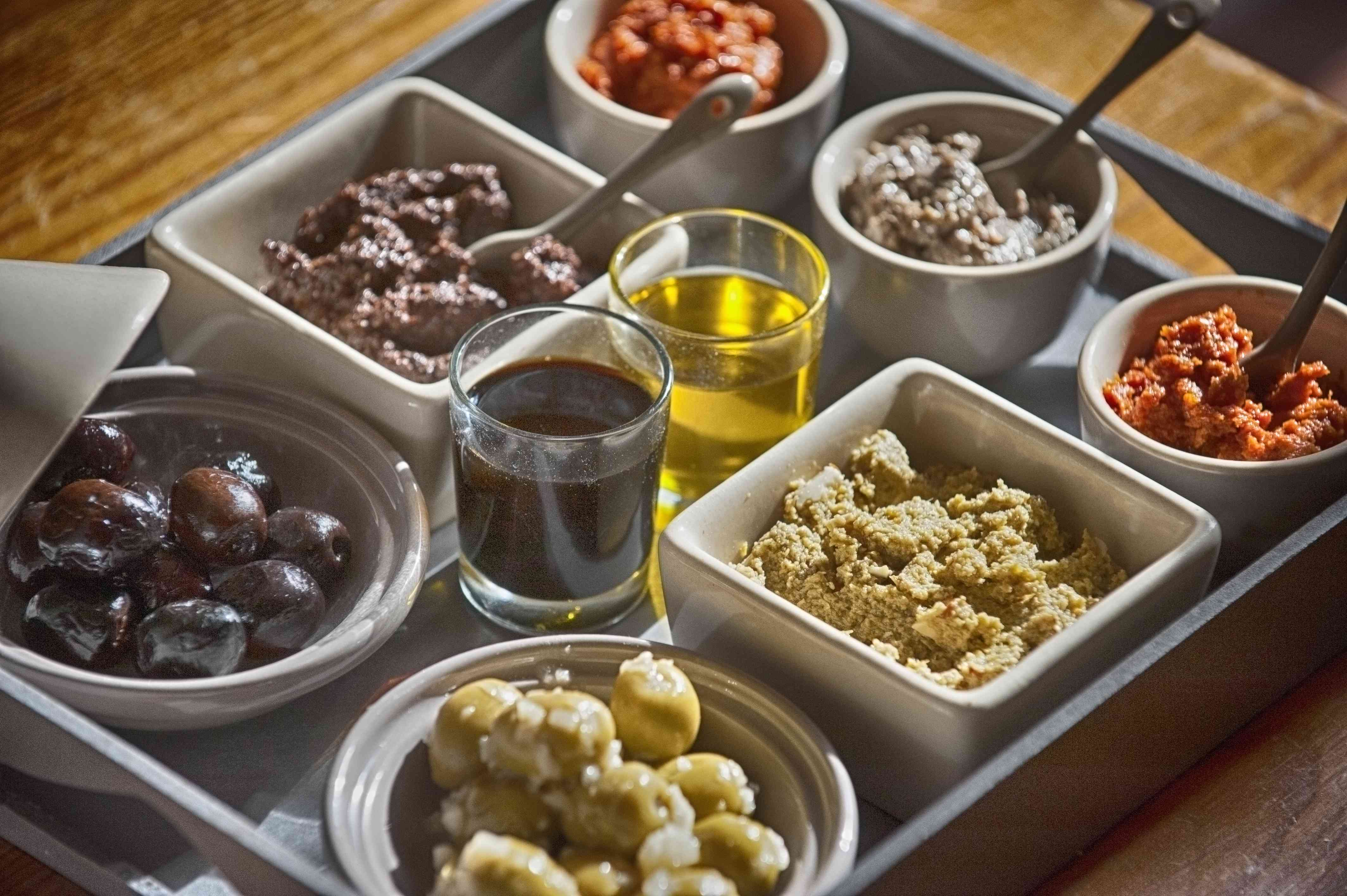 a tray of traditional provencal aperitifs - black and green olives, prepared with garlic; black tapenade, green tapenade, caviare de tomate, anchoiade (anchovy spread) olive oil and balsamic vinegar.