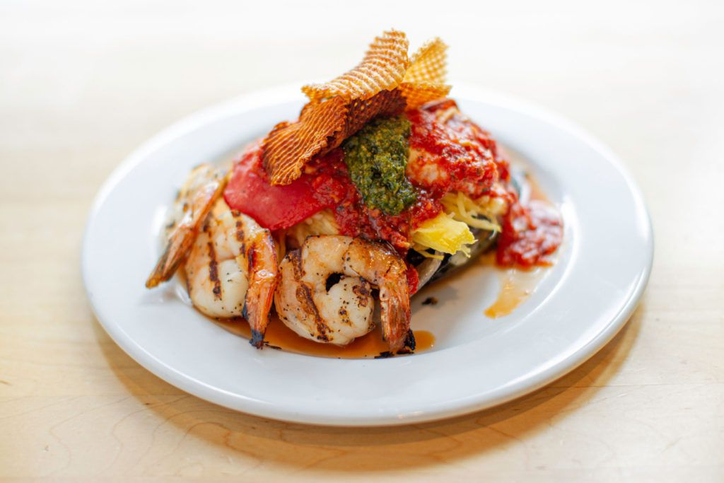 grilled shrimp topped with red sauce and pesto on a white plate