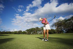 Hawaii, Maui, Wailea Gold Golf Course, Female golfer swinging golf club.