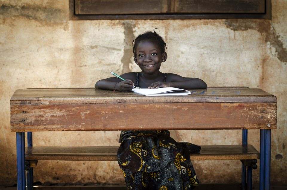 Malawian schoolgirl sitting at a desk with pen and paper
