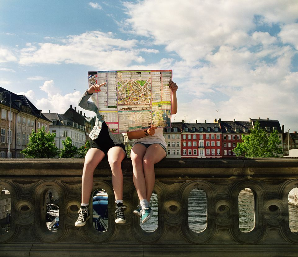 Two teenage girls sitting on bridge holding city map in front of them. Copenhagen city center.