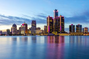 The skyline of Detroit in the evening, with pink lights on many of the buildings for breast cancer awareness. The skyline is reflecting off the Detroit River.