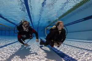 Scuba diving student and instructor practicing a skill