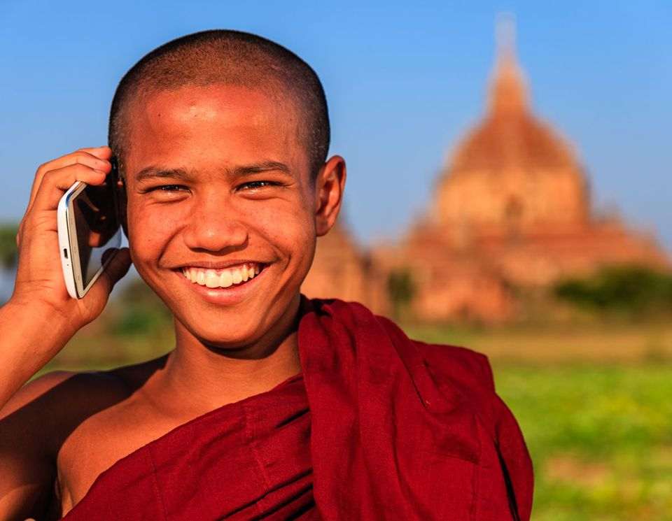 Young Buddhist monk using cellphone in Bagan, Myanmar