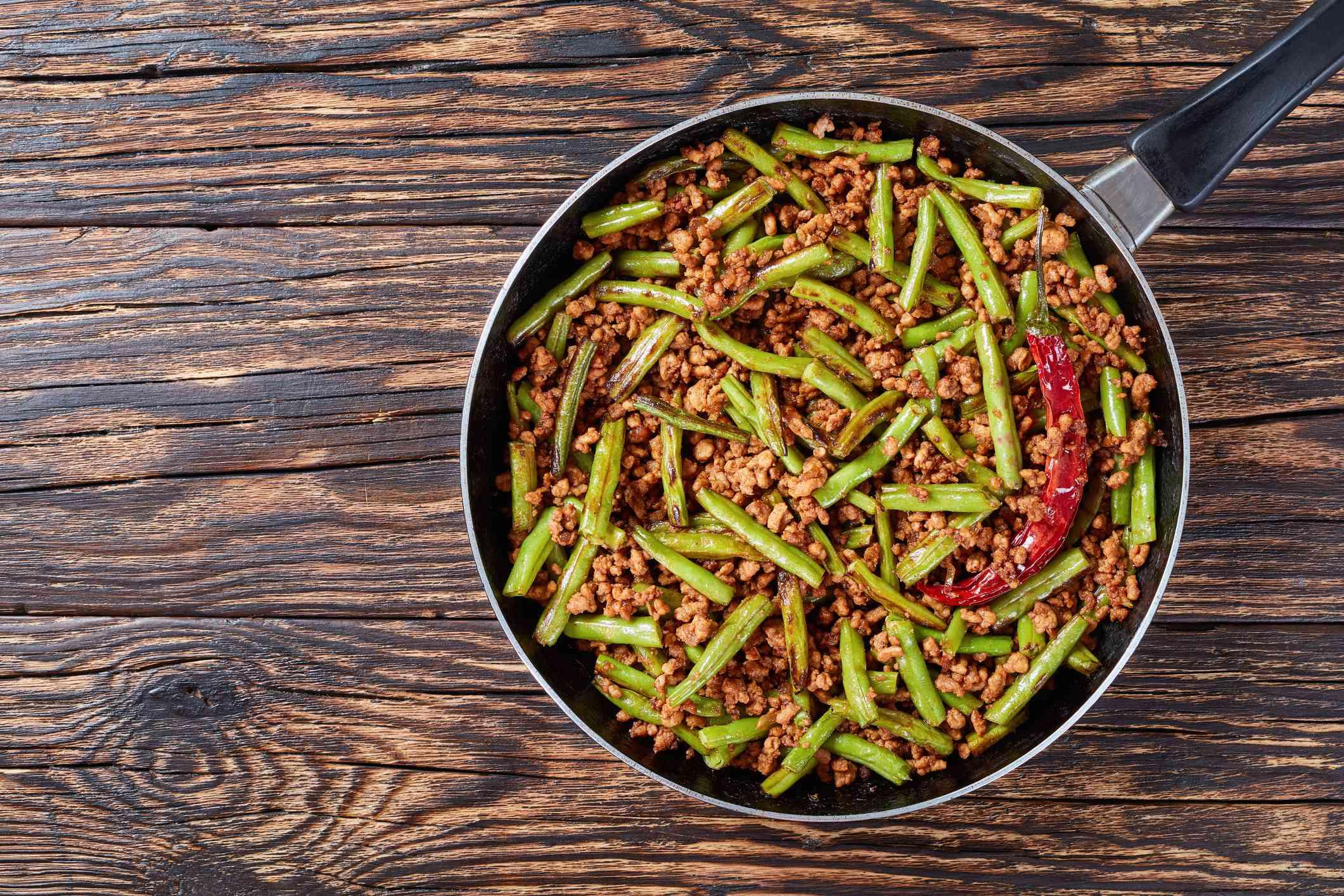 Szechuan Stir Fried Green Beans with ground pork in a skillet