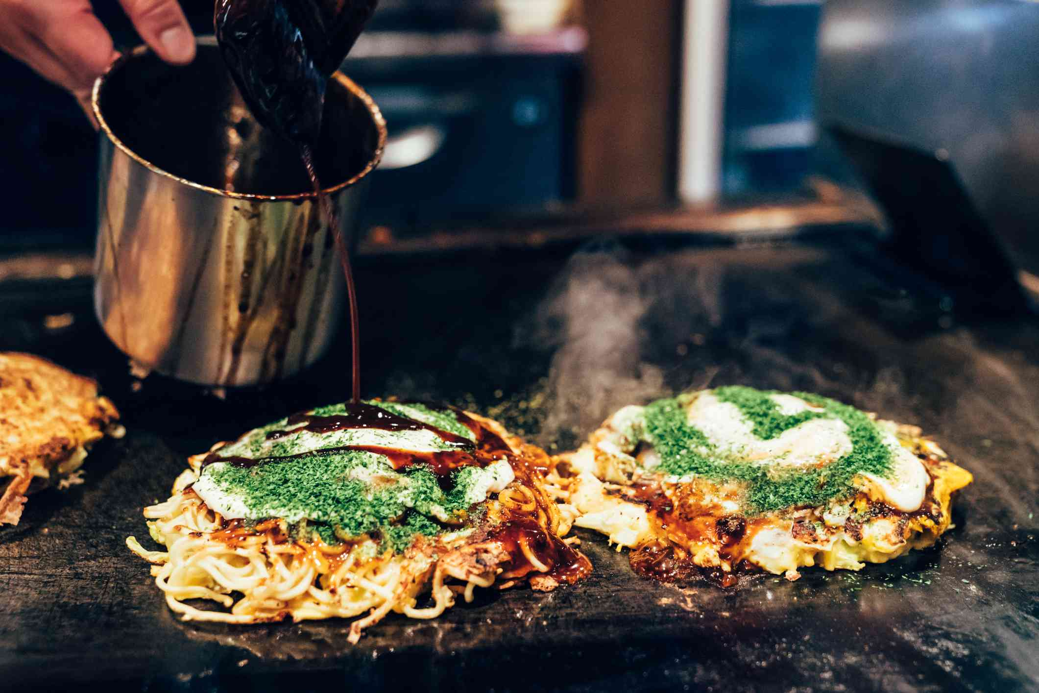Two Okonomiyaki on a grill. One is getting brown sauce poured on it