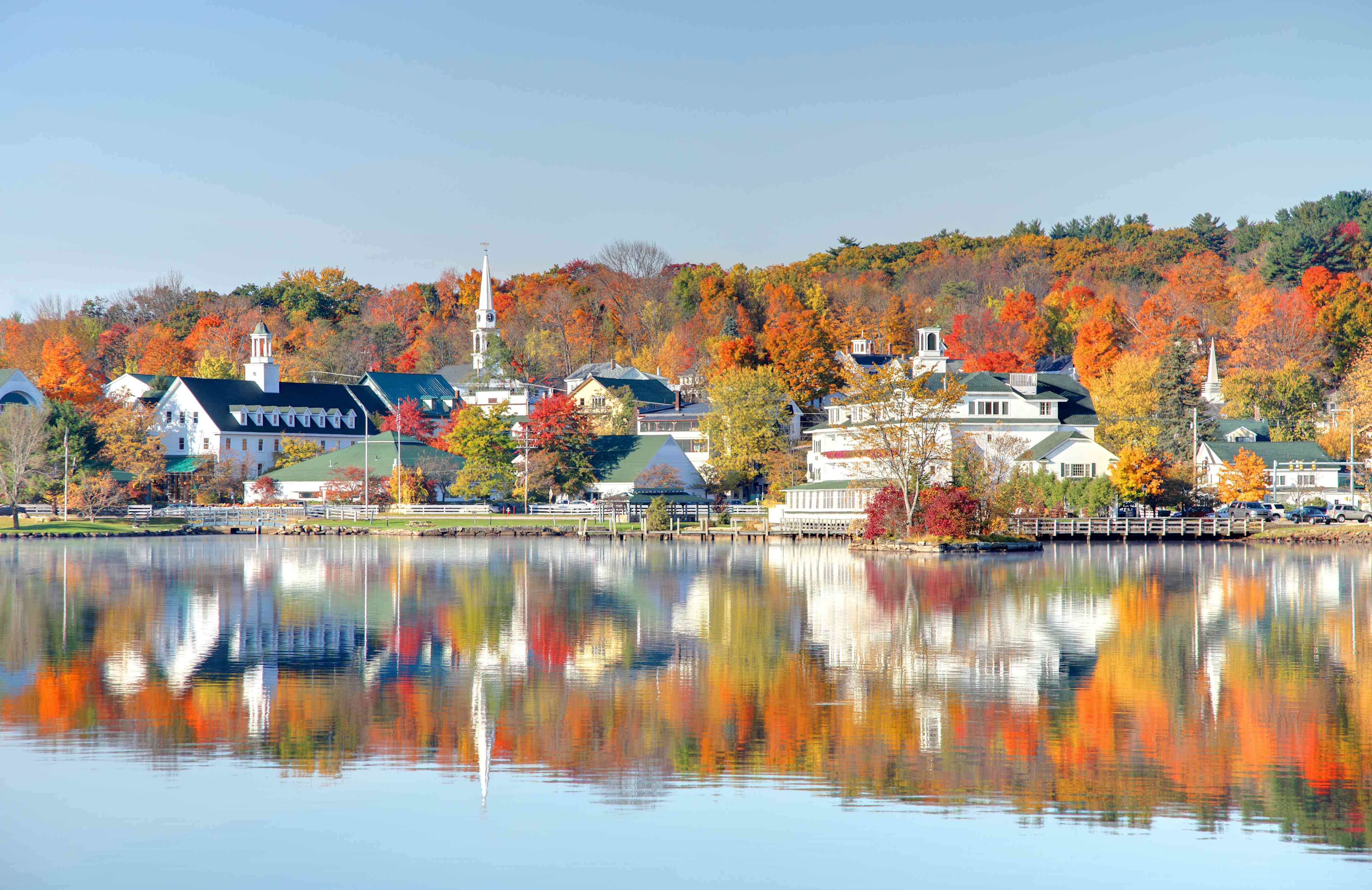 Autumn foliage and houses reflection along the shores of Lake Winnipesaukee in Meredith, New Hampshire