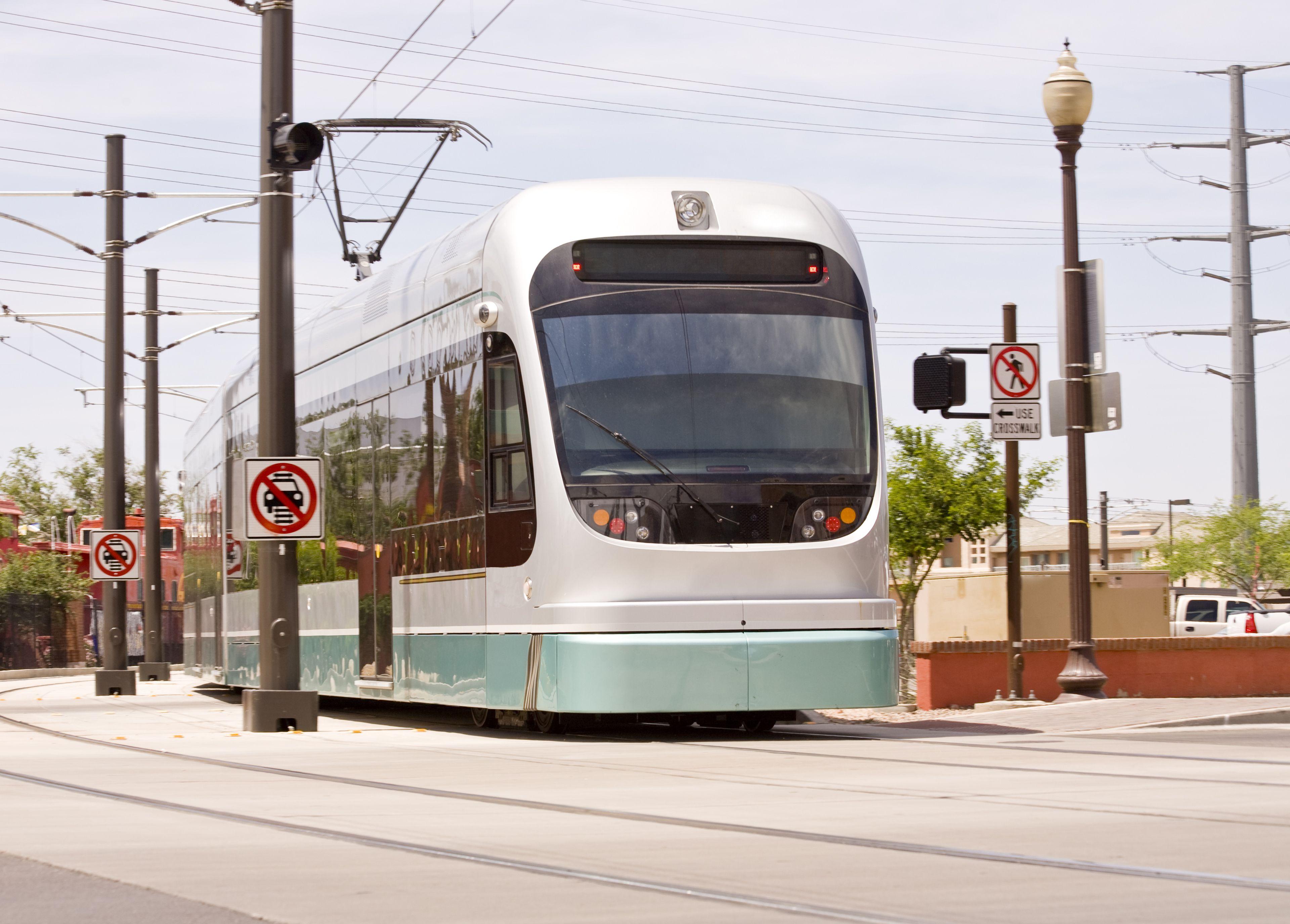A green and white car of the Phoenix Metro Light Rail Train