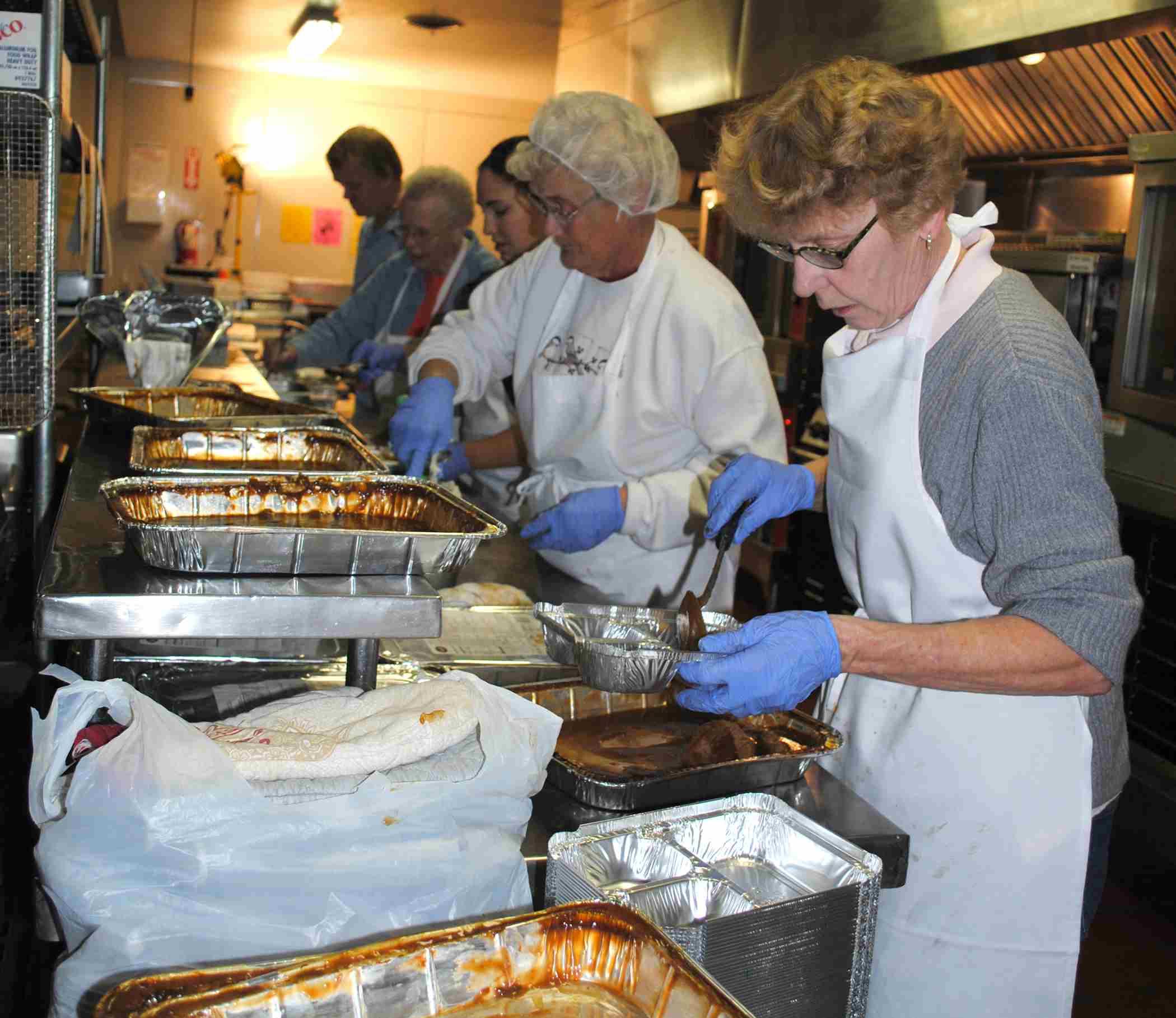 Comidas sobre Ruedas voluntarios llevan a cabo la preparación de alimentos para las comidas de Acción de Gracias.