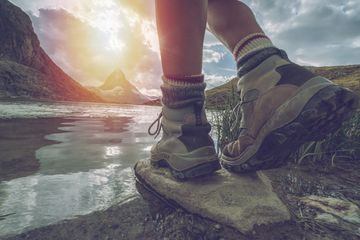 shot of woman's legs from calf down in hiking boots in nature