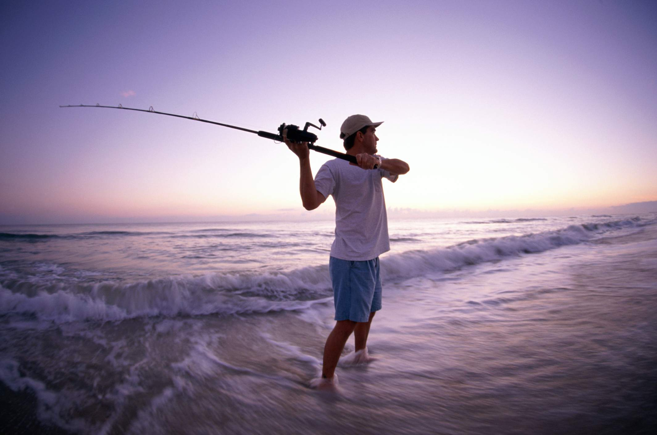 Fisherman casting from the beach