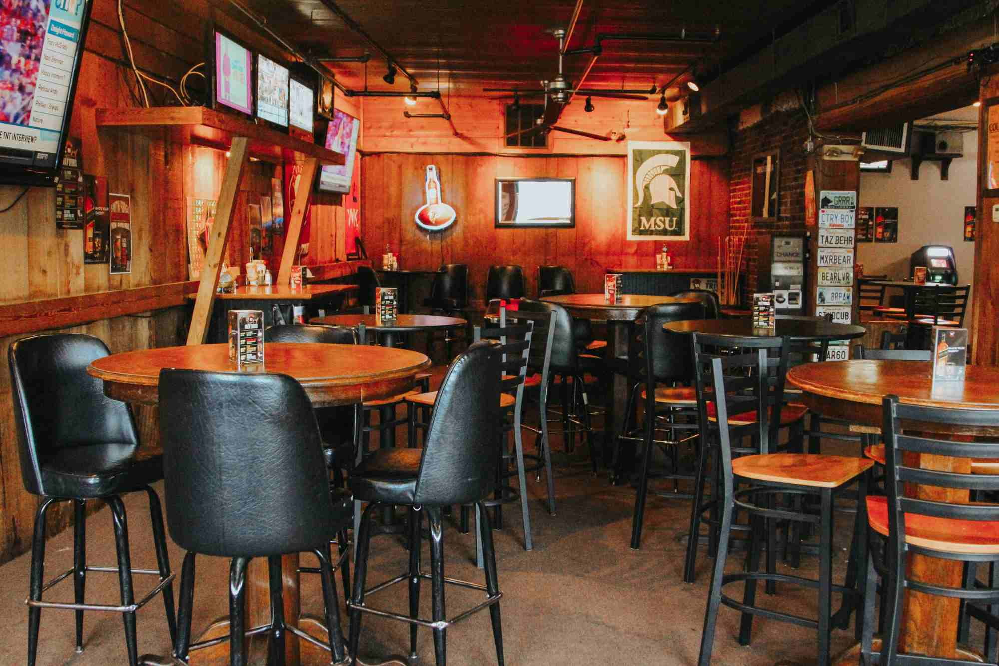 Tables and chairs situated near televisions at Woofs Atlanta.