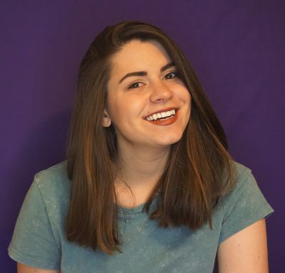 Kate Morgan (a white woman with brown hair) wearing a T-shirt and smiling in front of a purple background