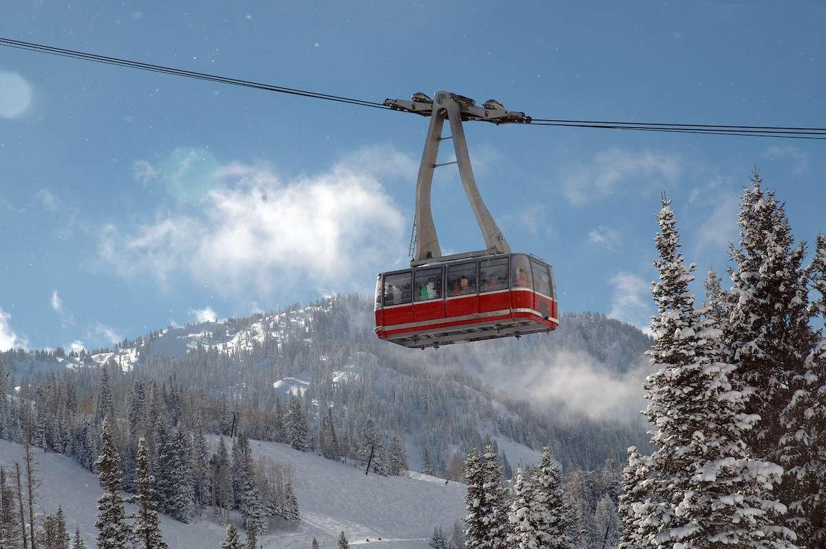 A large ski tram glides past a snow peak