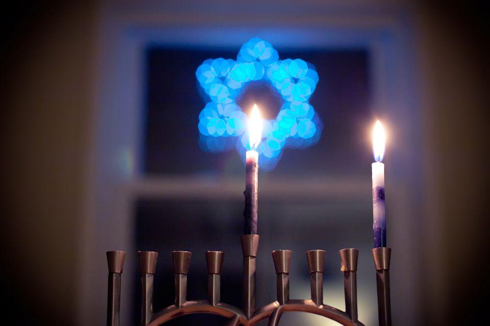 Una menorá con 2 velas encendidas con una estrella de David azul detrás de ella