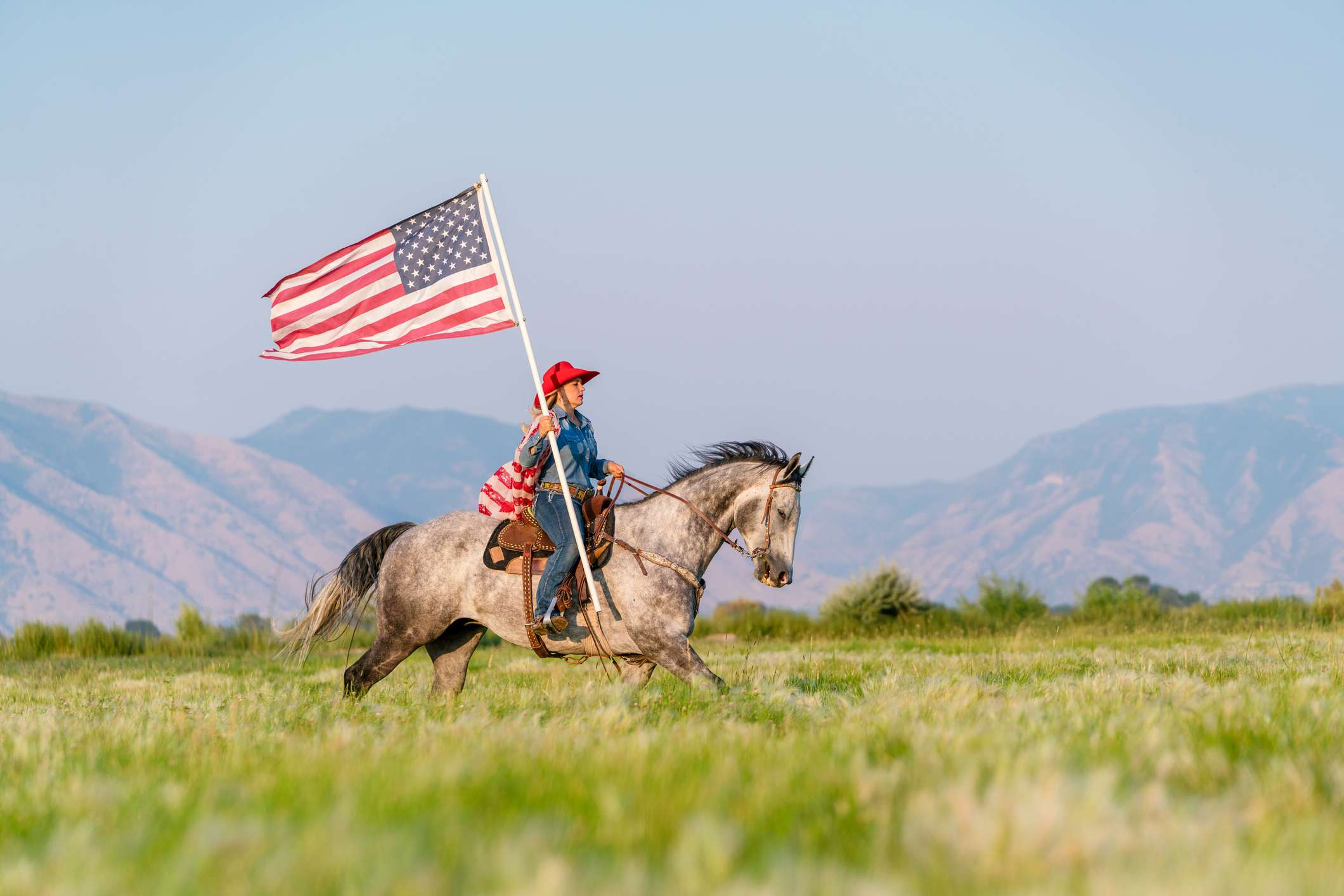 Young cowgirl wearing an American flag riding a horse