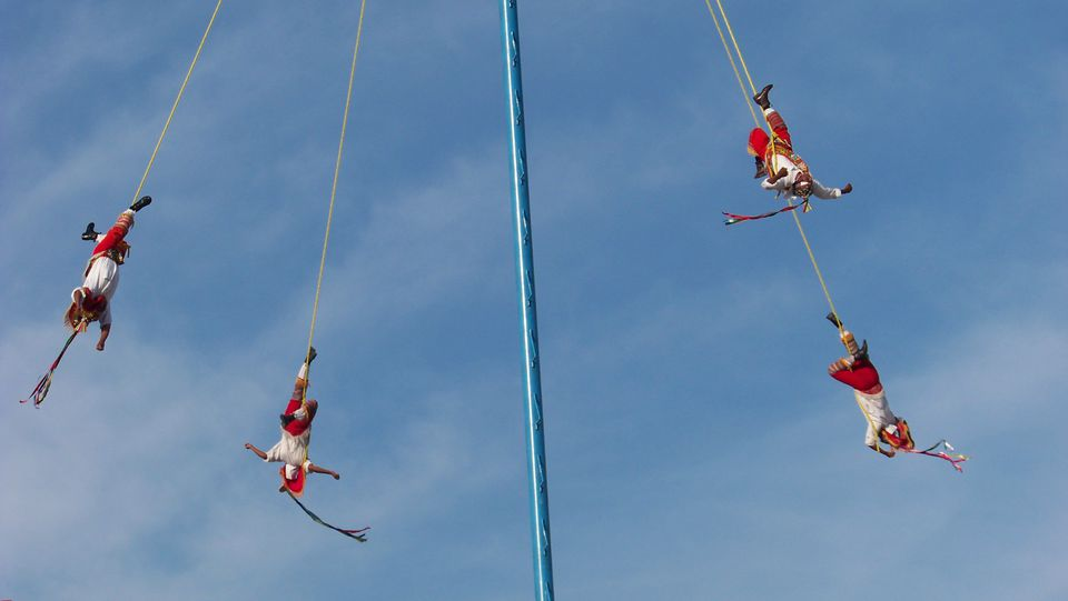 Men circling on a pole.