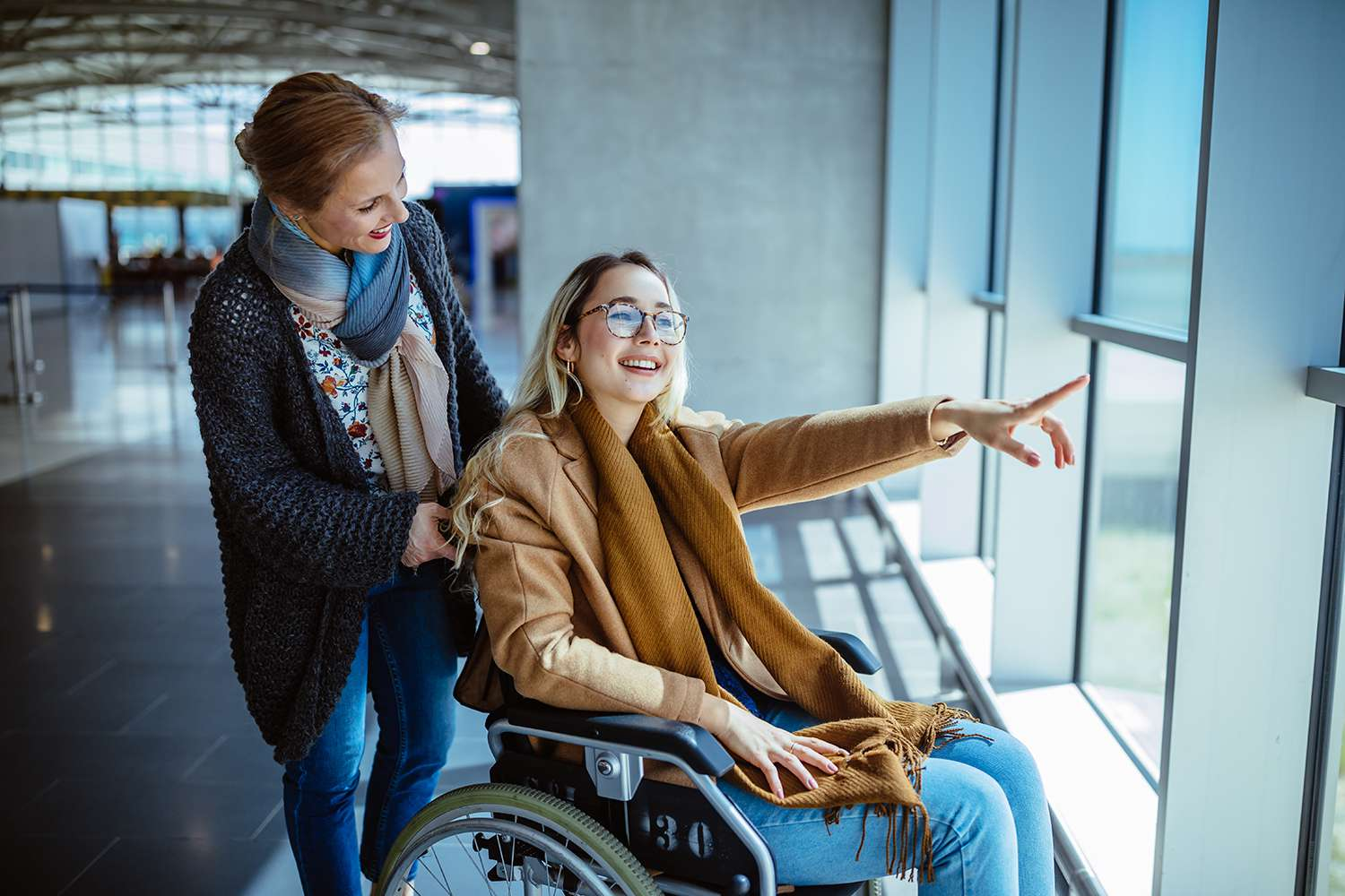 Young disabled woman on wheelchair and mother waiting at airport