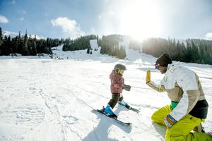 Happy father giving high five to his young boy as he is teaching him how to ski during the winter.