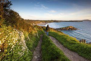 Walker on the Pembrokeshire coast path at Whitesands near St Davids, Wales