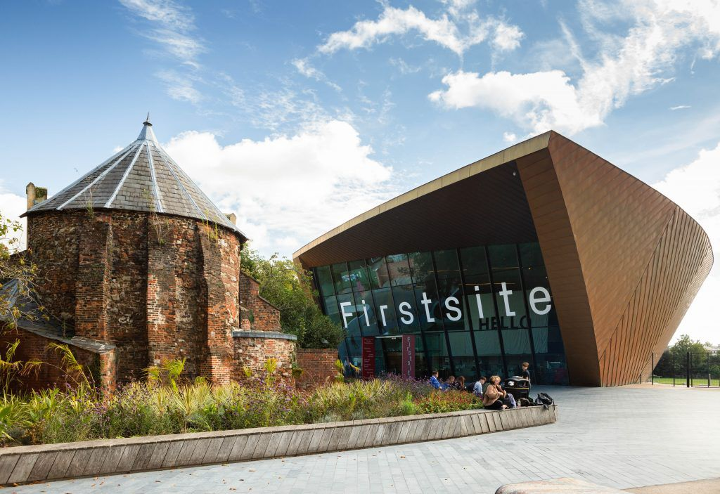 old brick structure next to the modern, glass-windowed building of Firstsite gallery