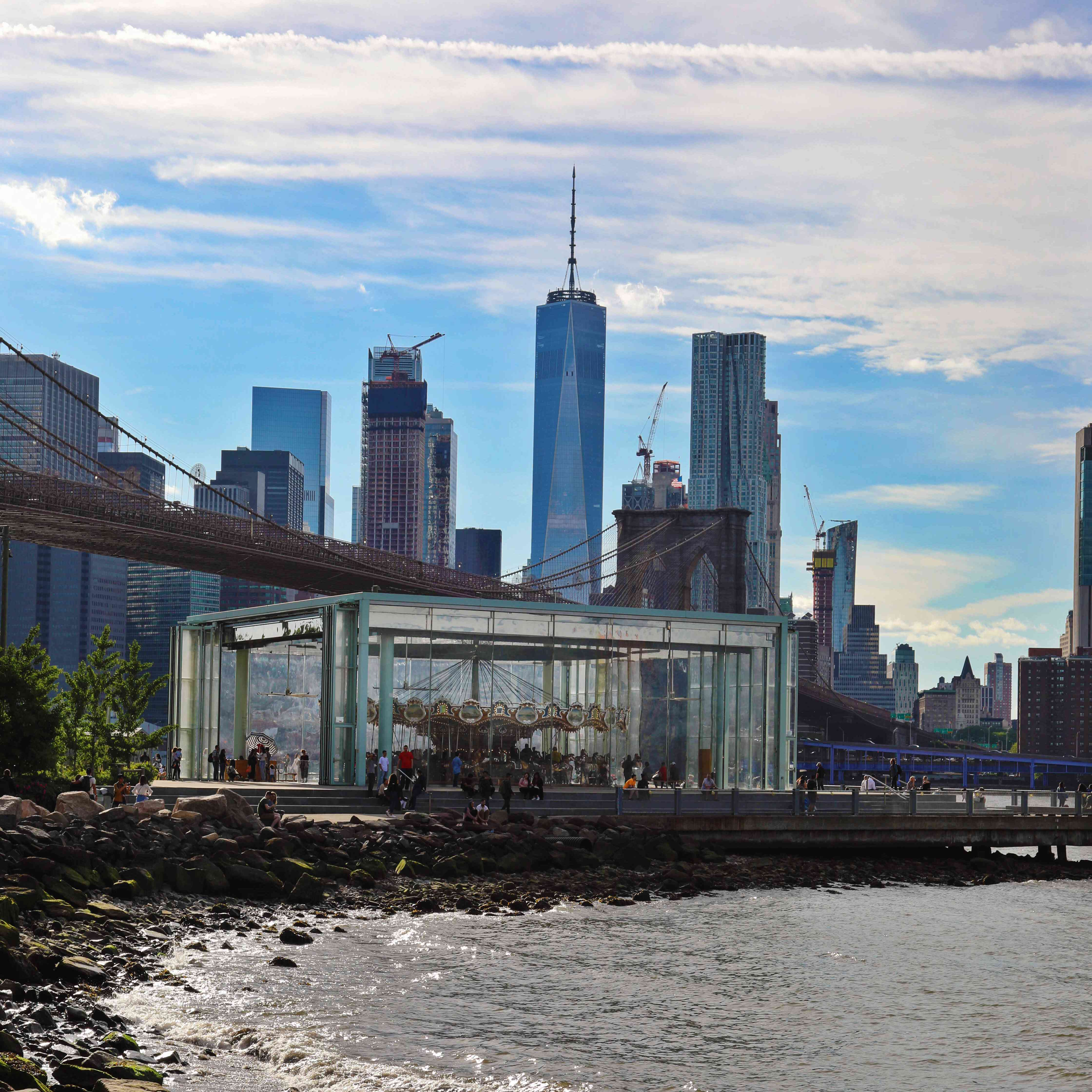 A view of Jane's Carousel with the Manhattan Skyline and the Brooklyn Bridge behind it