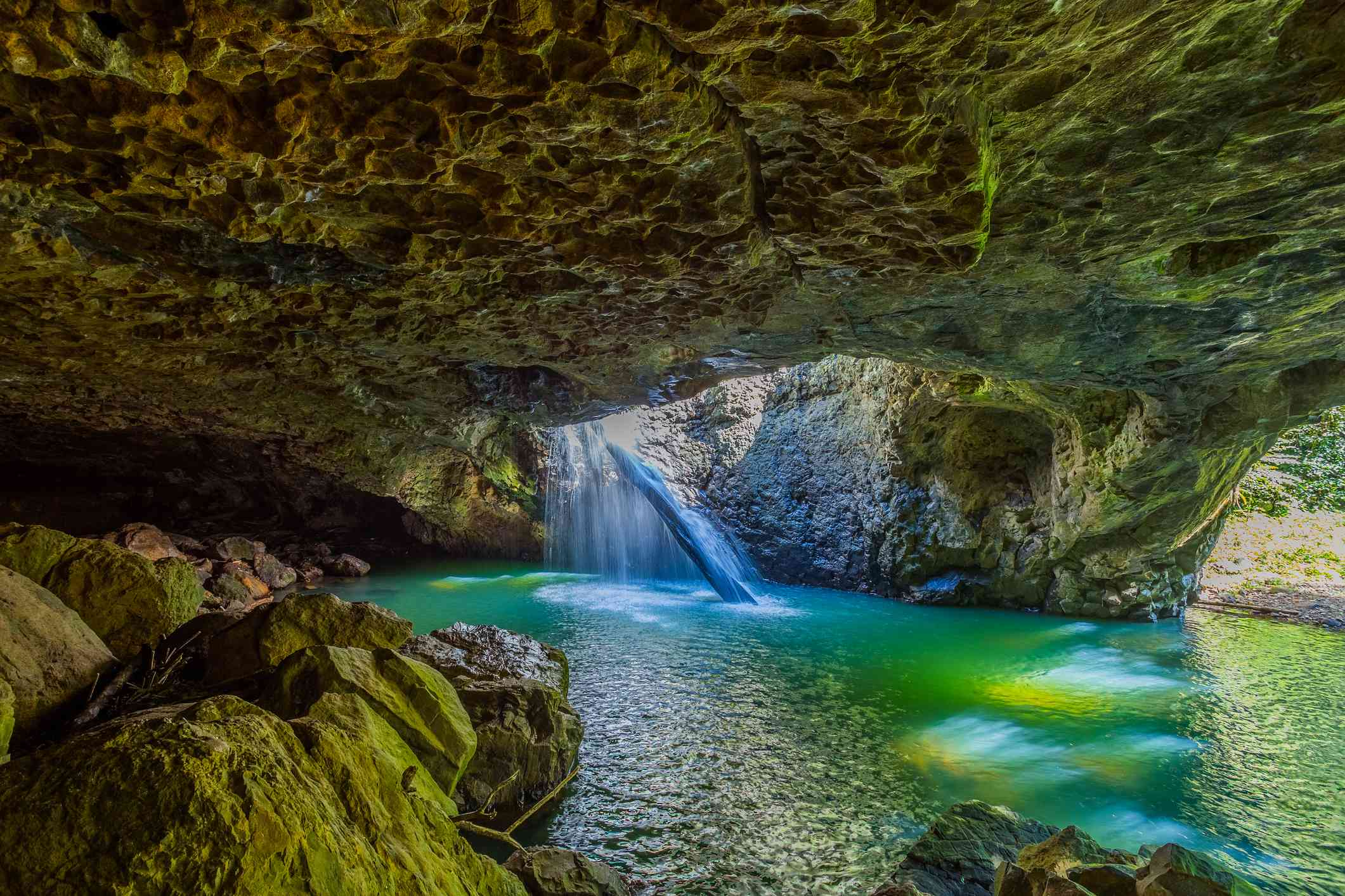 Inside of the cave of Natural Bridge, with turquoise water falling down through an opening in the roof of the cave