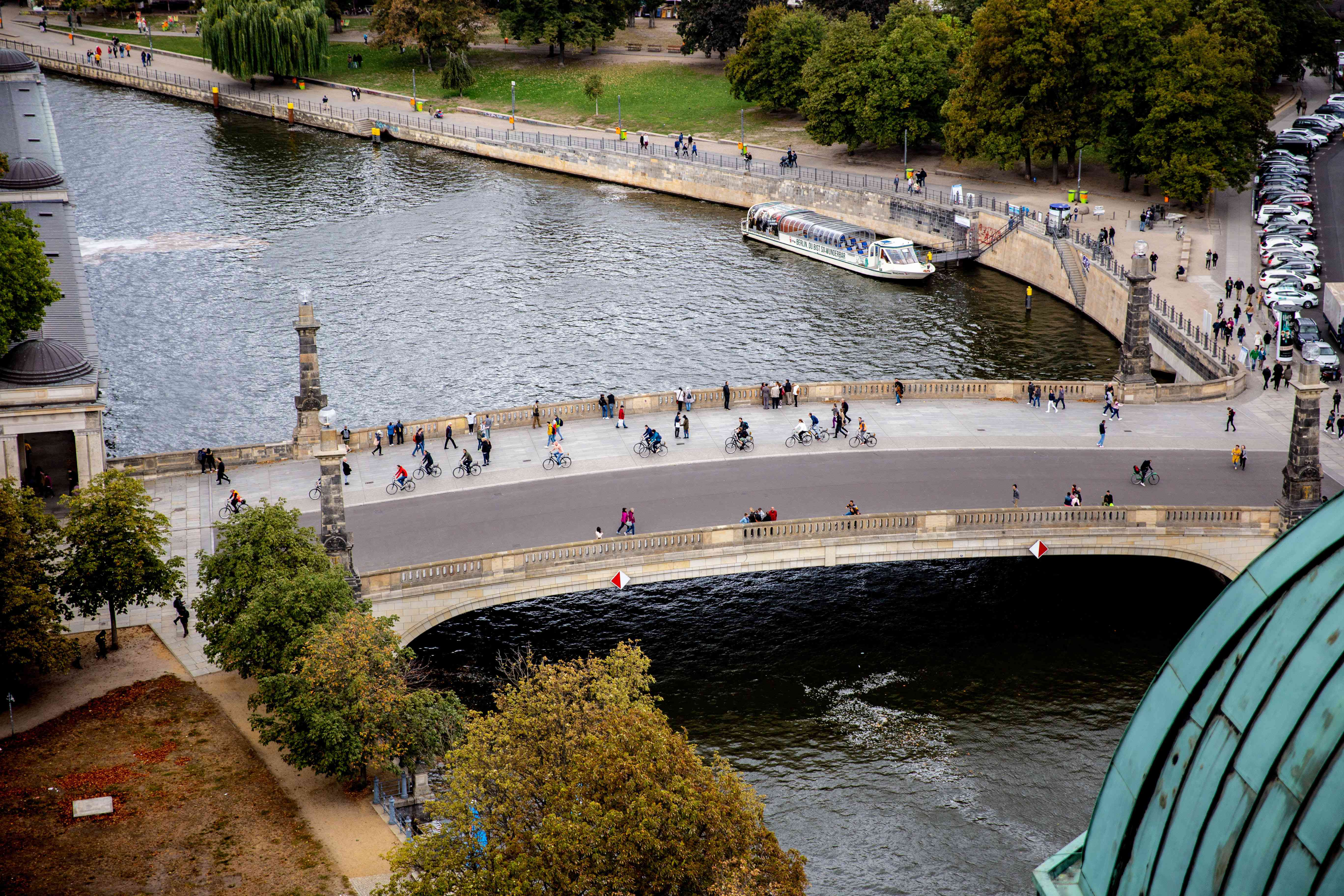 a tourist boat docked by a pedestrian bridge on the river spree