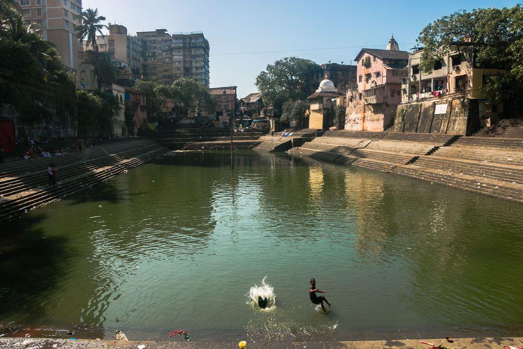 Two people jumping into the water and splashing at Banganga Tank