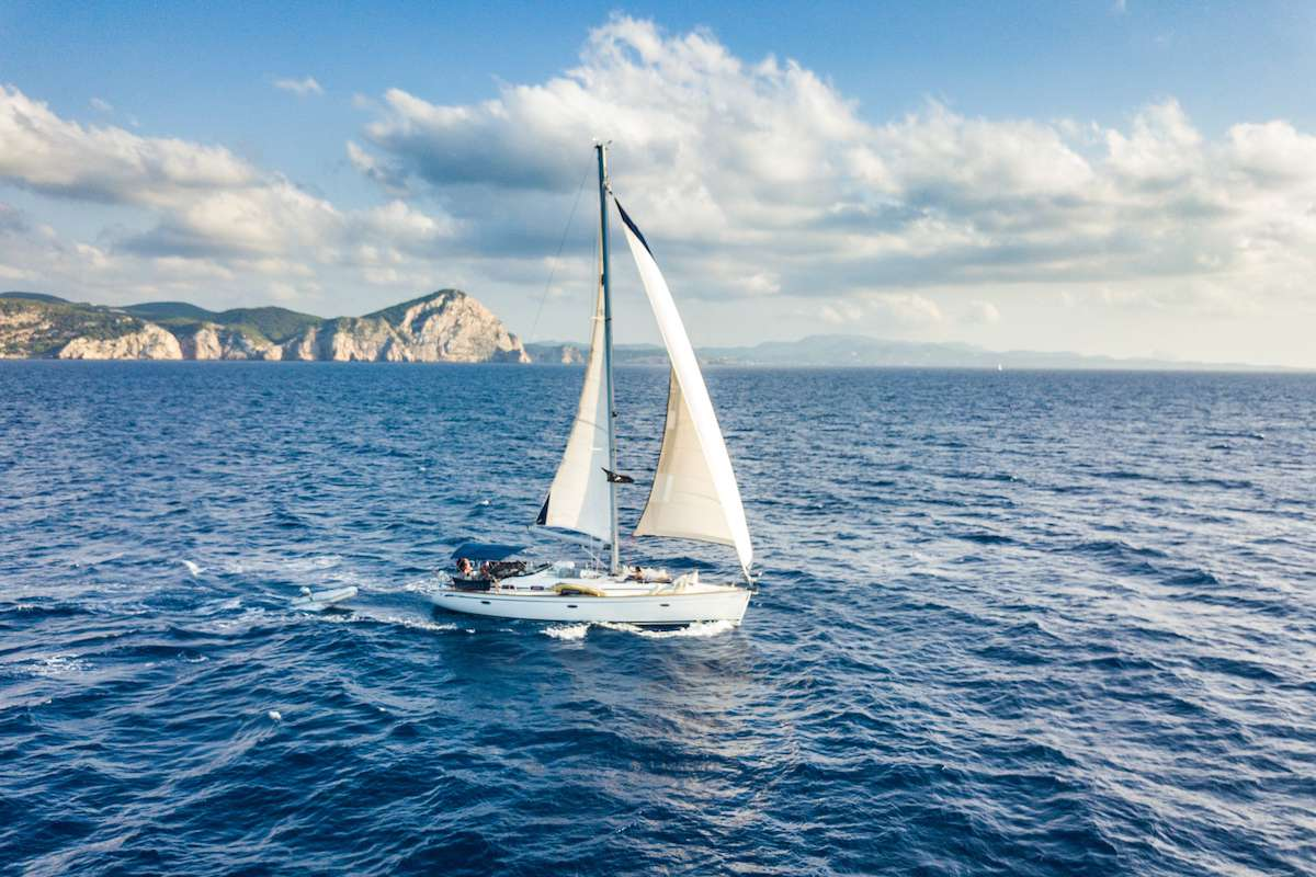 A white sailboat on the blue waters of the Mediterranean with a coastline in the background