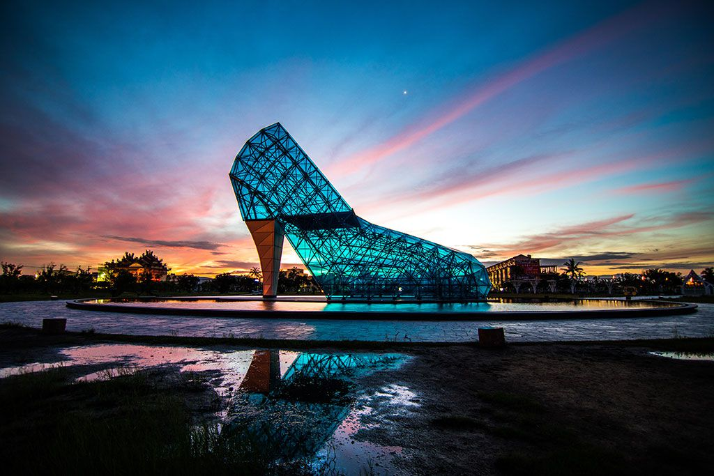 large glass building shaped like a high-heel shoe photograhed at sunset