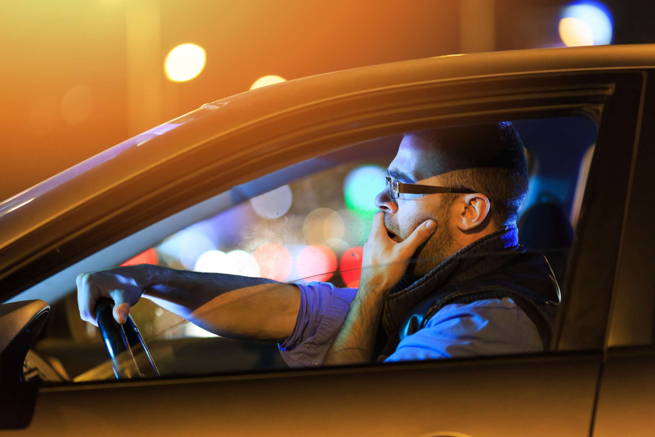Side view of young man with eyeglasses sitting inside of his car and yawning.
